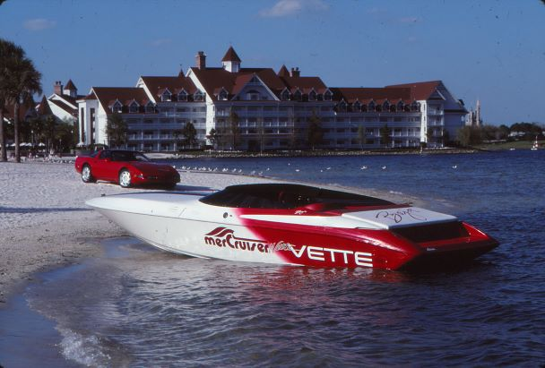 A red corvette is parked on a beach at the water's edge next to a red and white speed boat. In the background is a hotel resort.