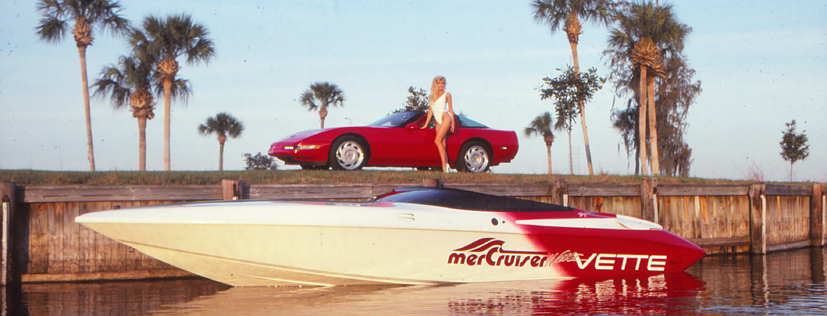 A model stands next to a red Corvette surrounded by palm trees. In the foreground a red and white speed boat is floating in the water.